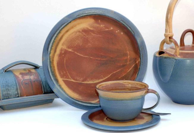 Eine kleine Tasse mit passendem Henkel auf einem kleinen Teller mit einem größeren Teller und eine rechteckige Butterdose und eine Teekanne