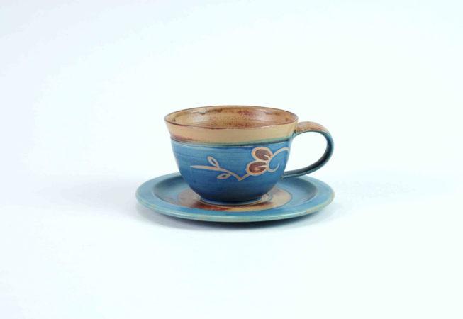 Eine kleine Tasse für einen Kaffee oder Tee auf einer flachen Untertasse. Die Tasse ist blau und am Rand und innen braun und bemalt