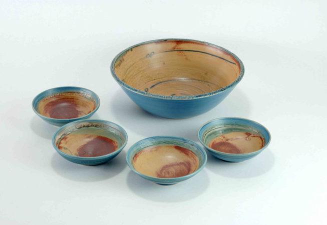 Eine große blaue Schüssel mit einem geprägten Rand steht neben vier kleinen Schalen für einen Nachtisch oder ein Dessert