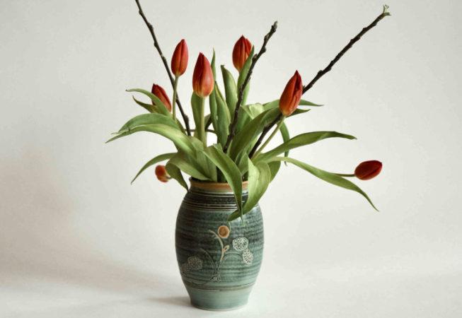 Ein länglich-runder Topf ist gefüllt mit einem Blumenstrauß mit Tulpen. Die Öffnung der Vase ist weit.