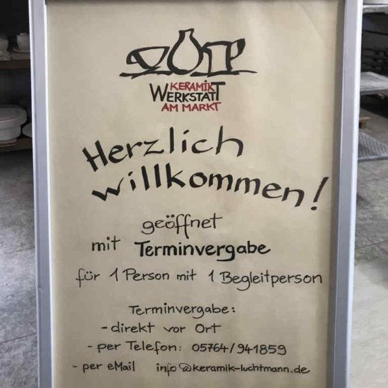 In einem Aufstellen ist ein Plakat. Es informiert über den Besuch in der Keramikwerkstatt mit Terminvergabe