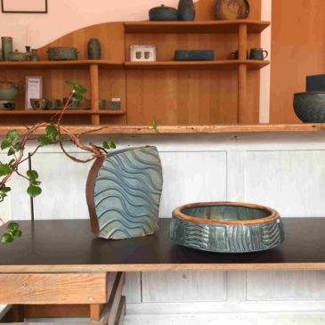 In einem Laden sind Unikate ausgestellt. In einer flachen Vase mit Wellendekor ist ein Zweig dekoriert. Daneben ist eine große Schale ebenfalls mit einem Wellendekor.