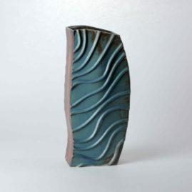 Eine hohe geschwungene aufgebaute Vase. Das Einzelstück hat zwei braune Seiten und zwei blaue Seiten. Die blauen Seiten haben aufgelegte Tonwülste, die an fließendes Wasser erinnern sollen.