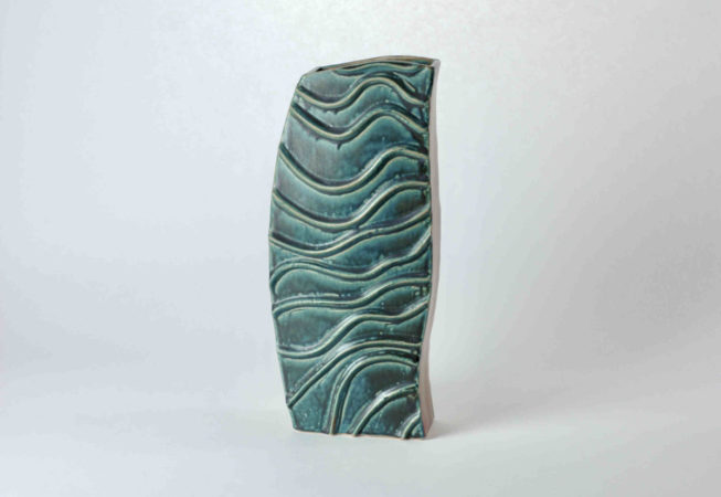 """Eine hohe Vase mit auffälligen Wellen auf zwei Seiten. Das Unikat heißt """"Blaue Welle"""", die erhabenen Strukturen auf den blauen Seiten erinnern an fließendes Wasser."""