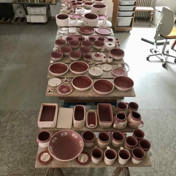 Auf einem Tisch in einer Werkstatt sind voll bestückte Bretter mit teilweise glasierter Keramik.