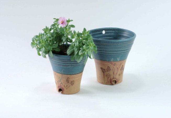 In einem kleinen Wandhängetopf ist eine Pflanze direkt eingepflanzt, daneben steht ein Topf in der großen Ausführung