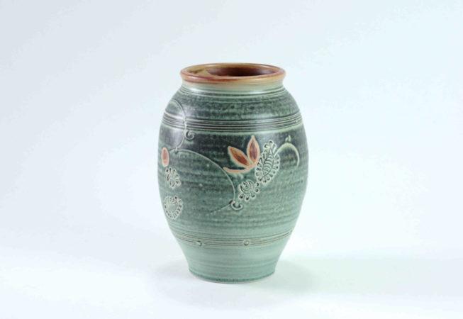 Eine grüne Vase mit Linien und Ornamenten als leichte Dekoration