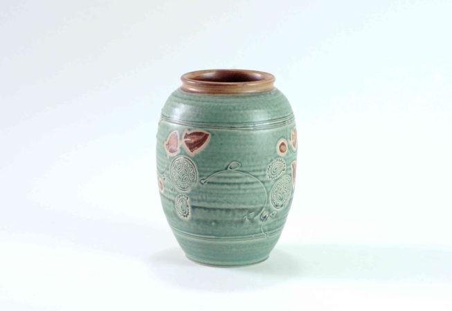 Eine grüne Vase mit Verzierungen und Schattierungen