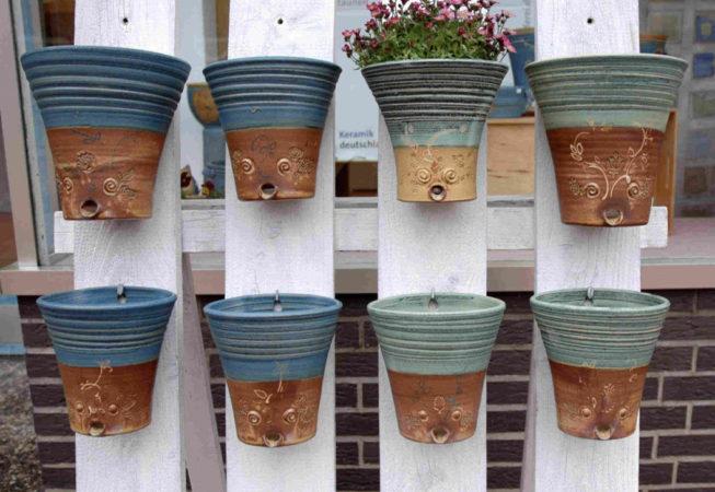 große und kleine Pflanztöpfe sind an einem Lattenständer angebracht