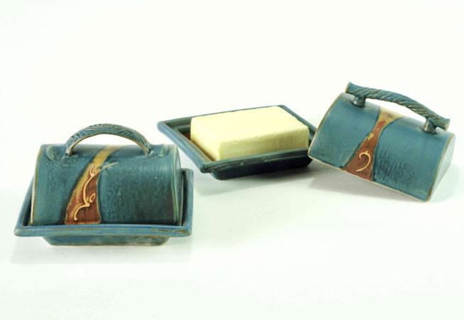 zwei blaue Butterdosen, die linke Butterdose ist geschlossen und hat eine strukturierten Henkel. Die Butterdose auf der rechten Seite ist offen und es liegt ein Stück Butter im Unterteil, das Oberteil hat einen strukturierten Stangengriff und steht daneben mit einer Seite auf einer Ecke vom Unterteil.