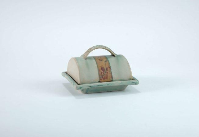 eine grüne Butterdose aus zwei Teilen die aufeinander sitzen, das obere Teil hat einen geprägten Henkel und unter dem Henkel ist eine Sand-Braun Farbene Fläche mit einer kleinen dunklen Malerei darauf