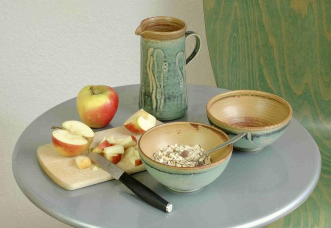 Kleine Schalen für Müsli, groß genug für die Haferflockenmischung und klein geschnittene Äpfel, dahinter steht ein kleiner Krug