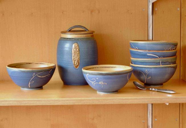 In einem Holzregal stehen blaue Müslischalen und eine große Dose für Müsli