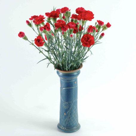 Eine schlanke gerade Vase ist gefüllt mit einem Strauß Nelken
