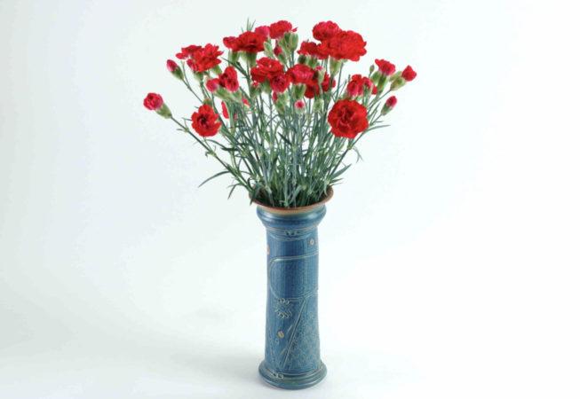 Eine schlanke blaue Vase mit einem kStrauß roter Nelken