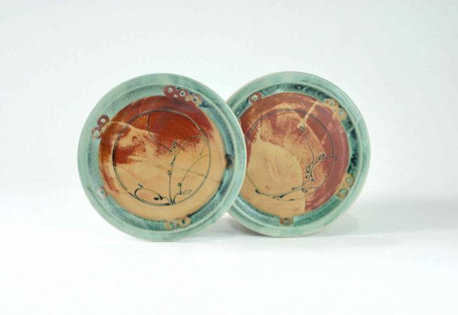 Zwei frontal abgebildete Mittelteller mit grünem Rand und Dekor auf den unterschiedlich gezeichneten braunen Flächen