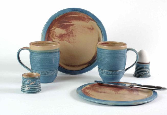 Zwei Mittelteller blau mit schlicht- brauner Fläche harmonieren mit großen blauen Henkelbecher und Eierbechern