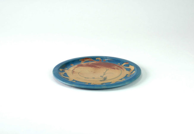 Flacher Teller mittelgroß mit Dekoren der Mitte ist er braun und hat einen blauen Rand mit Ornamenten