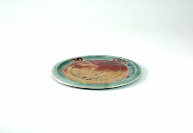 Ein flacher grüner Teller mit gemaltem Dekor und einer braunen Fläche in der Mitte